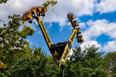 """In this photo made, visitors to Kennywood Park riding the """"Aero 360"""" are seen above the treetops as the ride lifts and spins them at the amusement park in West Mifflin, Pa. Visitors have been slow to return to U.S. theme parks that saw their seasons interrupted by the coronavirus crisis, causing some parks to reduce their operating days, slash ticket prices and close early for the year"""