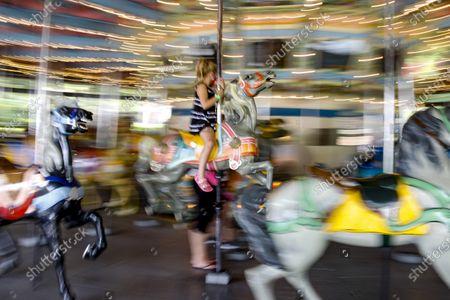 In this photo made with a slow shutter speed, a youngster rides on a carousel horse on the Merry-Go-Round at Kennywood Park in West Mifflin, Pa. Visitors have been slow to return to U.S. theme parks that saw their seasons interrupted by the coronavirus crisis, causing some parks to reduce their operating days, slash ticket prices and close early for the year