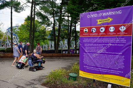 In this photo made, a group of visitors arriving at Kennywood Park make their way past the signs warning of COVID-19 restrictions and protocols at the amusement park in West Mifflin, Pa. Visitors have been slow to return to U.S. theme parks that saw their seasons interrupted by the coronavirus crisis, causing some parks to reduce their operating days, slash ticket prices and close early for the year