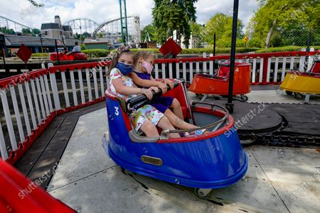 """In this photo made, four-year-olds Emberc-Claire Suskin, left and Josephine Kellner Klain wear their required protective masks as they ride the """"Whippersnapper"""" in the Kiddieland section of Kennywood Park in West Mifflin, Pa. Visitors have been slow to return to U.S. theme parks that saw their seasons interrupted by the coronavirus crisis, causing some parks to reduce their operating days, slash ticket prices and close early for the year"""