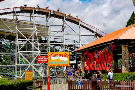 """In this photo made, people line up to ride the historic """"Thunderbolt"""" as roller coaster cars start a decent down one of the slopes at Kennywood Park in West Mifflin, Pa. Visitors have been slow to return to U.S. theme parks that saw their seasons interrupted by the coronavirus crisis, causing some parks to reduce their operating days, slash ticket prices and close early for the year"""