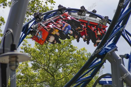 """In this photo made, riders of the """"Phantoms Revenge"""" roller coaster are inverted as they go through a loop during the ride at Kennywood Park in West Mifflin, Pa. Visitors have been slow to return to U.S. theme parks that saw their seasons interrupted by the coronavirus crisis, causing some parks to reduce their operating days, slash ticket prices and close early for the year"""