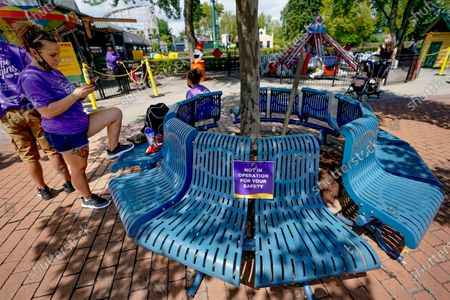 In this photo made, signs mark off parts of a bench to promote social distancing to help prevent the spread of COVID-19 in a seating area at Kennywood Park in West Mifflin, Pa. Visitors have been slow to return to U.S. theme parks that saw their seasons interrupted by the coronavirus crisis, causing some parks to reduce their operating days, slash ticket prices and close early for the year
