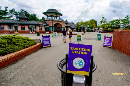 In this photo made, a couple people make their way through informational signs after passing a hand sanitization station at the entrance area of Kennywood Park in West Mifflin, Pa. Visitors have been slow to return to U.S. theme parks that saw their seasons interrupted by the coronavirus crisis, causing some parks to reduce their operating days, slash ticket prices and close early for the year