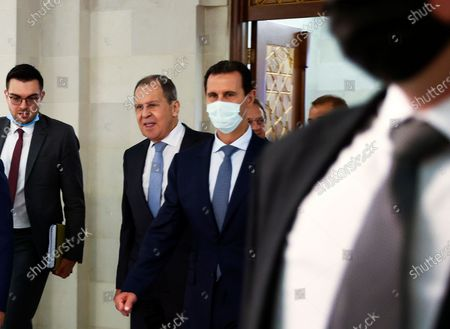 In this photo released by Russian Foreign Ministry Press Service, Russian Foreign Minister Sergey Lavrov, second left, and Syrian President Bashar al-Assad, center, enter a hall for their talks in Damascus, Syria, . Russia's foreign minister has met with Syrian President Bashar Assad shortly after landing in the Syrian capital on his first visit since 2012. Russia has been a close ally of Assad in Syria's long and bloody nine-year-long civil war, lending his government in Damascus vital military, economic and political support