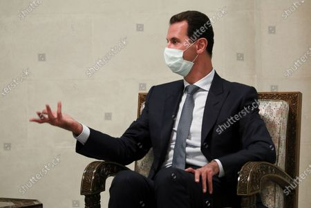 In this photo released by Russian Foreign Ministry Press Service, Syrian President Bashar al-Assad gestures while speaking to Russian Foreign Minister Sergey Lavrov during their talks in Damascus, Syria, . Russia's foreign minister has met with Syrian President Bashar Assad shortly after landing in the Syrian capital on his first visit since 2012. Russia has been a close ally of Assad in Syria's long and bloody nine-year-long civil war, lending his government in Damascus vital military, economic and political support