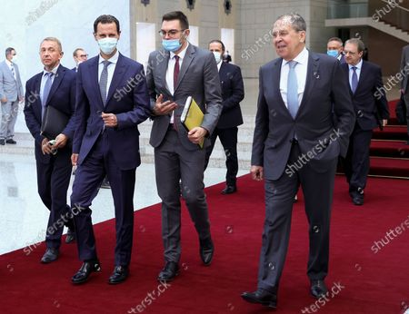 In this photo released by Russian Foreign Ministry Press Service, Russian Foreign Minister Sergey Lavrov, right, and Syrian President Bashar al-Assad, second left, walk after their talks in Damascus, Syria, . Russia's foreign minister has met with Syrian President Bashar Assad shortly after landing in the Syrian capital on his first visit since 2012. Russia has been a close ally of Assad in Syria's long and bloody nine-year-long civil war, lending his government in Damascus vital military, economic and political support