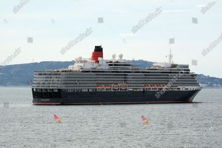 Wind surfers pass the Cunard ship Queen Elizabeth laid up in Weymouth Bay Dorset due to no sailings because of the Coronavirus crisis in