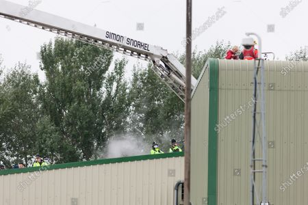 Greater Manchester Police look on as negotiators talk to a lone Animal Rebellion protester after she climed onto the roof of the Tulip slaughterhouse in Ashton-under-Lyne