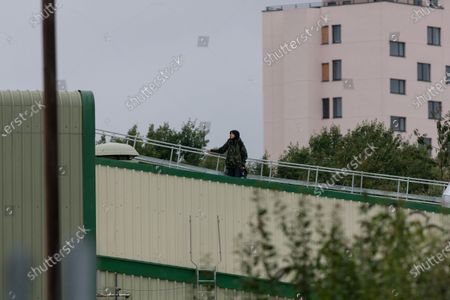 A lone Animal Rebellion protester on the roof of the Tulip slaughterhouse in Ashton-under-Lyne