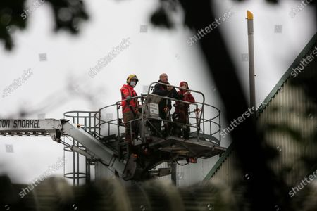 Police negotiators talk to a lone Animal Rebellion protester after she climed onto the roof of the Tulip slaughterhouse in Ashton-under-Lyne