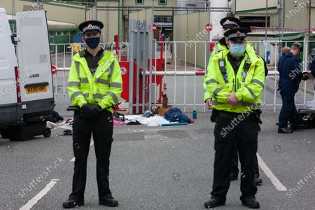 Police stand guard as Animal Rebellion activists are arrested at the Tulip slaughterhouse in Greater Manchester