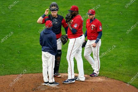 Minnesota Twins pitching coach Wes Johnson, left, along with catcher Ryan Jeffers and third baseman Josh Donaldson, right, visit at the mound with Michael Pineda in a baseball game against the Detroit Tigers, in Minneapolis