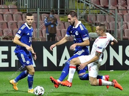 Bosnia's Elvir Koljic, centre, duels for the ball with Poland's Jacek Goralski during the UEFA Nations League soccer match between Bosnia-Herzegovina and Poland at the Bilino polje stadium in Zenica, Bosnia