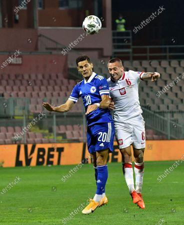 Poland's Jacek Goralski, right, jumps for the ball with Bosnia's Haris Hajradinovic during the UEFA Nations League soccer match between Bosnia-Herzegovina and Poland at the Bilino polje stadium in Zenica, Bosnia