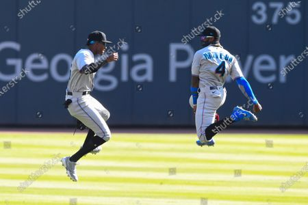 Miami Marlins outfielders Lewis Brinson and Monte Harrison (4) celebrate after the tenth and final inning of a baseball game against the Atlanta Braves, in Atlanta. Miami won 5-4
