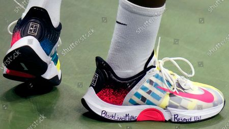 "Frances Tiafoe, of the United States, prepares to serve, as his tennis shoes display the words ""Black Lives Matter"" and Respect Us!"", during his match against Daniil Medvedev, of Russia, during the fourth round of the US Open tennis championships, in New York"