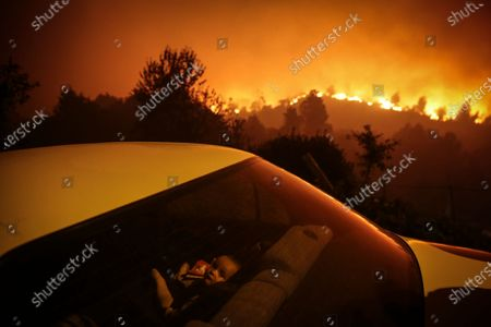 YEARENDER 2020  CLIMATE CHANGE   A child inside a car near a forest fire in Oliveira de Frades, northern Portugal, 07 September 2020. This forest fire mobilized 327 firemen, 103 land vehicules and 8 airplanes.