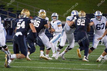 Quarterback Zach Wilson, center, looks to throw downfield as Navy defensive tackles Jackson Perkins (96) and Deondrae Williams (92) apply pressure during the first half of an NCAA college football game, in Annapolis, Md