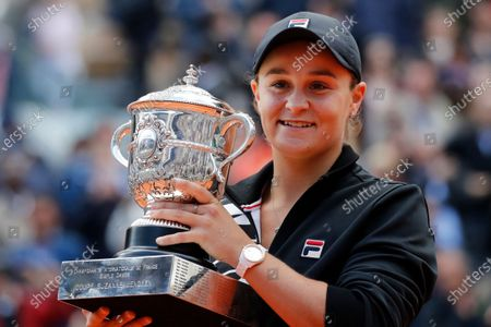 Australia's Ash Barty holds the trophy after winning the women's final match of the French Open tennis tournament at the Roland Garros stadium in Paris. Top-ranked Ash Barty will not defend her French Open title because of concerns over traveling during the COVID-19 pandemic