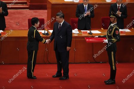 Chinese President Xi Jinping (C) shakes hands with vaccine researcher and People's Liberation Army (PLA) major general Chen Wei (L) during a meeting commending role models in the country's fight against the COVID-19 epidemic at the Great Hall of the People (GHOP) in Beijing, China, 08 September 2020. The ceremony was held to honour people who were involved in the fight against the COVID-19.
