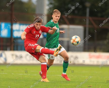Stock Picture of Anders Dreyer of Denmark clears the ball under pressure from Northern Ireland's Paul O'Neill; Ballymena Showgrounds, Ballymena, Antrim County, Northern Ireland; UEFA Under 21s Championship Qualifier, Group B, Northern Ireland versus Denmark.