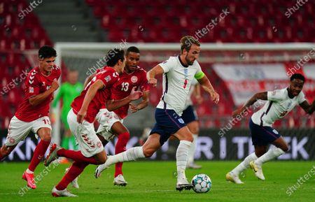 Harry Kane of England runs the ball as Christian Norgaard, Andreas Christensen and Mathias Jorgensen of Denmark chase him down