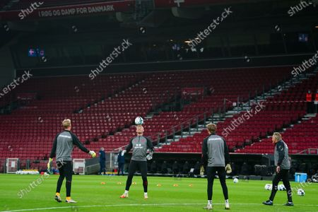 Stock Photo of Kasper Schmeichel of Denmark balances the ball on his head as he warms up alongside goalkeepers Jonas Lossl and Frederik Ronnow of Denmark before kick-off
