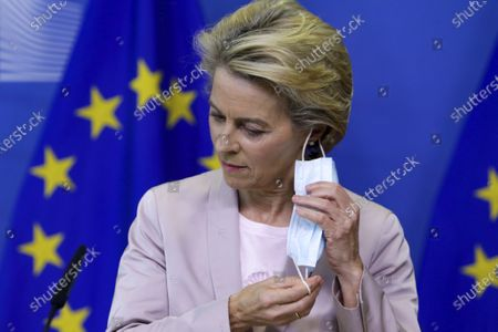 European Commission President Ursula von der Leyen takes off a a protective mask prior to making a press statement at EU headquarters in Brussels, . The European Union's executive commission has proposed European Commission vice-president Valdis Dombrovskis to take over the post of EU trade commissioner following the resignation of Ireland's Phil Hogan
