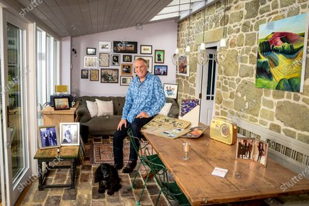 Stock Photo of Johnnie Walker 'My Haven' - Garden Room of his Dorset Home 24.10.2019 Mother's Bush Radio (c.1960s) Kiss in the Car Licence from Radio Caroline Scrapbooks that Johnnie's mother compiled in 1960s of his career Silver cup from Led Zepplin - presented to Johnnie after introducing them at Earls Court in 1970s Tiggy & Johnnie wedding photo MBE photo Johnnie, Tiggy (Johnnie's kids) Beth & Sam at Buckingham Palace Photo of Elton John handing Johnnie his Sony Gold award. Sony Gold award Jeager-LeCoultre watch given to Johnnie on his 70th birthday by Tiggy Cartoon of Johnnie & Peter Kay after they recorded a car-share radio show as they drove around Bolton  Photo of Radio Caroline Boat Dog Darcey a working Cocker Spaniel
