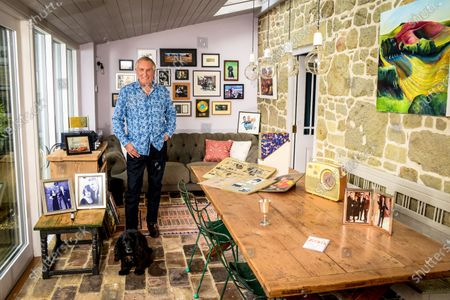 Stock Image of Johnnie Walker 'My Haven' - Garden Room of his Dorset Home 24.10.2019 Mother's Bush Radio (c.1960s) Kiss in the Car Licence from Radio Caroline Scrapbooks that Johnnie's mother compiled in 1960s of his career Silver cup from Led Zepplin - presented to Johnnie after introducing them at Earls Court in 1970s Tiggy & Johnnie wedding photo MBE photo Johnnie, Tiggy (Johnnie's kids) Beth & Sam at Buckingham Palace Photo of Elton John handing Johnnie his Sony Gold award. Sony Gold award Jeager-LeCoultre watch given to Johnnie on his 70th birthday by Tiggy Cartoon of Johnnie & Peter Kay after they recorded a car-share radio show as they drove around Bolton  Photo of Radio Caroline Boat Dog Darcey a working Cocker Spaniel