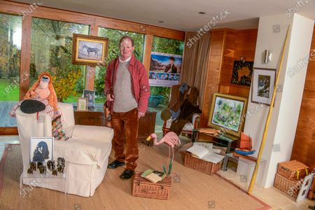 Stock Image of Michael Morpurgo 'My Haven' - Writing Room of his Devon Home 22.11.2019 Photo of Clare MM kept with him all his Army days. (Clare talk him out of staying in the Army and going to raise pigs on the farm. MM would have come a Brigadier if he'd stayed) Elephants from a Nun who fell in love with MM (he has a lot of elderly lady admirers) Photo Clare with NT War Horse when it came to the village. Picture by Judith Kerr she gave to MM when had Cancer MM War Horse costume he wears on stage Painting of 'Top Thorn' The Real War Horse that inspired the book 'Waiting for Anya' movie poster Farm  Picture by Gerald Scarf (Farms for City Children link) Photo Farms for City Children Pink Flamingo model (Flamingo Boy book) His trademark red jacket and black beret (story behind these) Poems by Ted Hughes Turtle from daughter Ros Orangutang from publisher Re: 'Runnuing Wild' Boat from Scilly Isles Narwhale Tusk (made of plastic) Book MM won at school when he was 6 yrs old Large Wooden Truck from Clare's Dad dated 1666