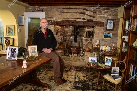 Sir Ranulph Fiennes 'My Haven'-Living Room of his Devon Home 29.10.2019 1.Childhood photo of Sir Ranulph Fiennes at 6 yrs old in South Africa2.Photo of his parents on their wedding day 3.Guns over fireplace - a memento of his army days. He joined the Royal Scots Greys (tanks) during the Cold War. He joined the SAS in 1965/1966. He was the youngest captain in the British Army. He fought marxist terrorists (1968-1970) and received the Sultan's Bravery Medal from the Queen.4. Omani Ceremonial Daggers5.Soapstone animals 6.Pink furry pig. He has taken it on all his expeditions. I think it's a sort of talisman/lucky charm. 7.Two fossils (an ammonite and a fossilised shell of some sort) There are an assortment of objects in the fireplace also linked to expeditions8. Guiness Book of Records- Certificate, Hall of Fame Gold Medal, Photo of Hall of Fame winners (including Paul McCartney and David Frost)9.Photo of Daughter Elizabeth on her horse 'Batman'10.Photo of Grandfather11. Film Canister containing the Tops of his Fingers and the Saw he used to cut them of with.12. His Books13. Snow Shoes