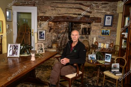 Stock Picture of Sir Ranulph Fiennes 'My Haven'-Living Room of his Devon Home 29.10.2019 1.Childhood photo of Sir Ranulph Fiennes at 6 yrs old in South Africa2.Photo of his parents on their wedding day 3.Guns over fireplace - a memento of his army days. He joined the Royal Scots Greys (tanks) during the Cold War. He joined the SAS in 1965/1966. He was the youngest captain in the British Army. He fought marxist terrorists (1968-1970) and received the Sultan's Bravery Medal from the Queen.4. Omani Ceremonial Daggers5.Soapstone animals 6.Pink furry pig. He has taken it on all his expeditions. I think it's a sort of talisman/lucky charm. 7.Two fossils (an ammonite and a fossilised shell of some sort) There are an assortment of objects in the fireplace also linked to expeditions8. Guiness Book of Records- Certificate, Hall of Fame Gold Medal, Photo of Hall of Fame winners (including Paul McCartney and David Frost)9.Photo of Daughter Elizabeth on her horse 'Batman'10.Photo of Grandfather11. Film Canister containing the Tops of his Fingers and the Saw he used to cut them of with.12. His Books13. Snow Shoes