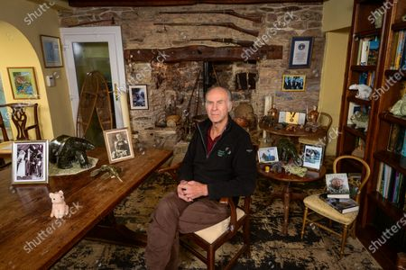 Stock Photo of Sir Ranulph Fiennes 'My Haven'-Living Room of his Devon Home 29.10.2019 1.Childhood photo of Sir Ranulph Fiennes at 6 yrs old in South Africa2.Photo of his parents on their wedding day 3.Guns over fireplace - a memento of his army days. He joined the Royal Scots Greys (tanks) during the Cold War. He joined the SAS in 1965/1966. He was the youngest captain in the British Army. He fought marxist terrorists (1968-1970) and received the Sultan's Bravery Medal from the Queen.4. Omani Ceremonial Daggers5.Soapstone animals 6.Pink furry pig. He has taken it on all his expeditions. I think it's a sort of talisman/lucky charm. 7.Two fossils (an ammonite and a fossilised shell of some sort) There are an assortment of objects in the fireplace also linked to expeditions8. Guiness Book of Records- Certificate, Hall of Fame Gold Medal, Photo of Hall of Fame winners (including Paul McCartney and David Frost)9.Photo of Daughter Elizabeth on her horse 'Batman'10.Photo of Grandfather11. Film Canister containing the Tops of his Fingers and the Saw he used to cut them of with.12. His Books13. Snow Shoes