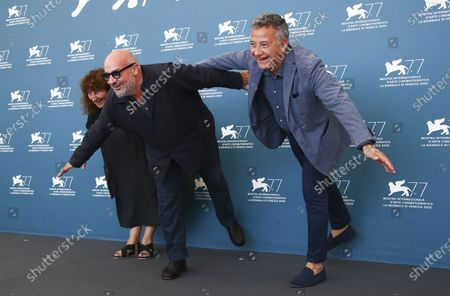 Stock Photo of Producer Donatella Palermo, from left, director Gianfranco Rosi and producer Paolo Del Brocco pose for photographers at the photo call for the film 'Notturno' during the 77th edition of the Venice Film Festival in Venice, Italy
