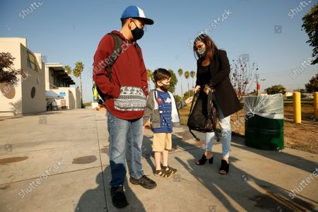 Stock Picture of In the age of the COVID-19 pandemic administrative assistant Lilia Cosio puts a backpack on her 6-year-old son Leo Perez as brother 12-year-old Rudy Perez waits before entering the L.A. City Department of Recreation & Parks Delano Recreation Center for the start of the Safer at Parks Alternative Learning Centers and After School Program which aims to provide working-poor mothers and families with child care, studying and program assistance for children at 50 parks citywide. Los Angeles City Council President Nury Martinez and Anthony Paul Diaz, executive officer L.A. City Department of Recreation & Parks announced the program is free to any Elementary and Middle School students through December from 8 a.m. to 7 p.m. and students are provided breakfast, lunch and a snack. Van Nuys on Thursday, Sept. 3, 2020 in Los Angeles, CA. (Al Seib / Los Angeles Times