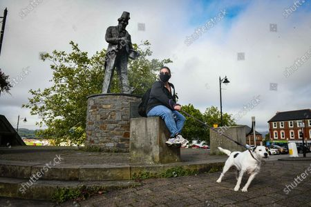 Stock Photo of Caerphilly, Wales, UK. Resident, Claire Evans sits by the Tommy Cooper statue in the town of Caerphilly in south Wales, which has gone into lockdown along with it's wider borough area, after what is being described as a rapid increase in coronavirus cases. The Welsh government announced that from 6pm on Tuesday people will not be able to leave or enter the area without good reason, along with other restrictive measures.