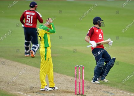 Australia's Ashton Agar, center, reacts as England's Dawid Malan, right, and Jonny Bairstow, left, run between the wickets to score during the third Twenty20 cricket match between England and Australia, at the Ageas Bowl in Southampton, England