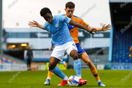 Josh Wilson-Esbrand of Manchester City under pressure from Corey O'Keeffe of Mansfield Town