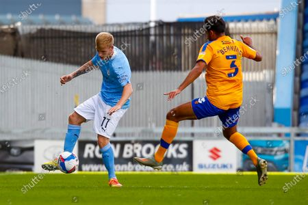 Malvind Benning of Mansfield Town attempts to block a through ball by Sammy Robinson of Manchester City