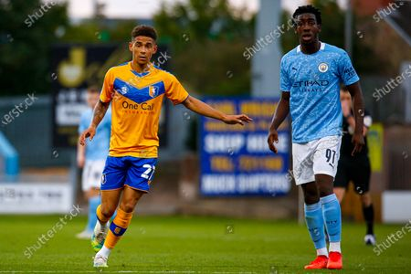 Stock Image of Tyrese Sinclair of Mansfield Town marks Josh Wilson-Esbrand of Manchester City