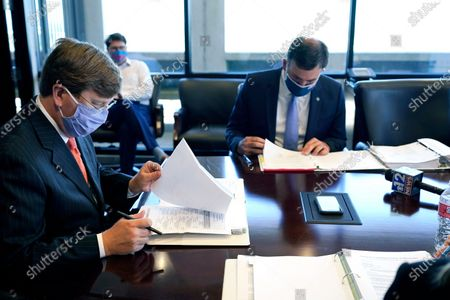 Mississippi Gov. Tate Reeves, left, reviews a sample ballot while Secretary of State Michael Watson, right, reads the names of those persons who have qualified to run for president on the fall election ballot during a meeting of the State Board of Election Commissioners, in Jackson, Miss. Kanye West will appear as a presidential candidate on Mississippi's ballot in November, after being approved as a qualified candidate by the State Board of Election Commissioners on Tuesday