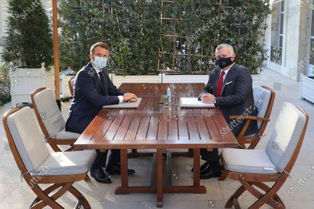 French President Emmanuel Macron, left, and Jordan's King Abdullah II, wearing face masks, pose during their meeting at the Elysee Palace in Paris
