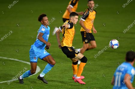Lewis Collins of Newport County is tackled by Elliot Bonds of Cheltenham Town.