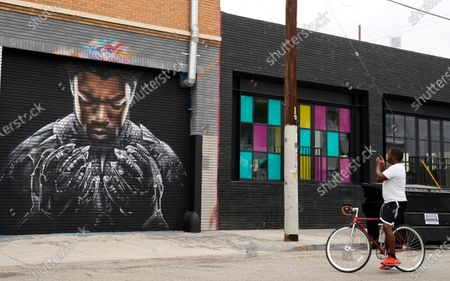 """Man stops to shoot a picture of a mural by artist Shane Grammer of late actor Chadwick Boseman's character T'Challa from the 2018 film """"Black Panther,"""", in Los Angeles. Boseman died Aug. 28 at age 43 after a four-year battle with colon cancer"""
