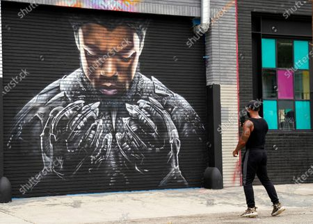 """Stock Image of Man stops to shoot a picture of a mural by artist Shane Grammer of late actor Chadwick Boseman's character T'Challa from the 2018 film """"Black Panther,"""", in Los Angeles. Boseman died Aug. 28 at age 43 after a four-year battle with colon cancer"""