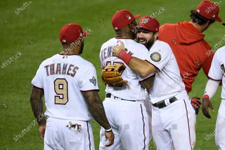 Stock Picture of Washington Nationals' Adam Eaton, front right, hugs Howie Kendrick after a baseball game against the Tampa Bay Rays, in Washington. At left is Eric Thames (9). The Nationals won 5-3