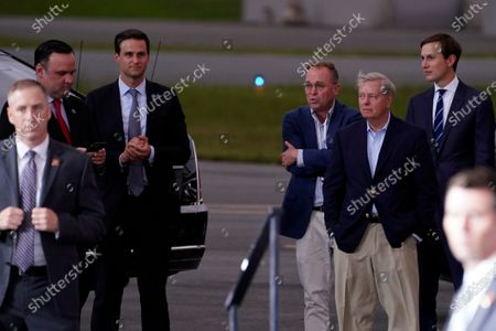White House social media director Dan Scavino, from left, White House aide John McEntee former acting chief of staff Mick Mulvaney, Sen. Lindsey Graham, R-S.C., and White House adviser Jared Kushner talk as President Donald Trump speaks during a campaign rally at Smith Reynolds Airport, in Winston-Salem, N.C