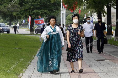 Women, holding North Korean national flags in hands, walk together, in Pyongyang. North Koreans mark Foundation Day with floral offerings at the foot of giant statues of late leaders Kim Il Sung and Kim Jong Il
